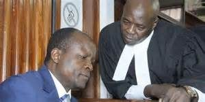 File photo- Okoth Obado consults his lawyer in court