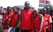 Kwale Girls' soccer team coach, Mukasa Amboko, poses with his players. The girls have won this year's SOYA awards