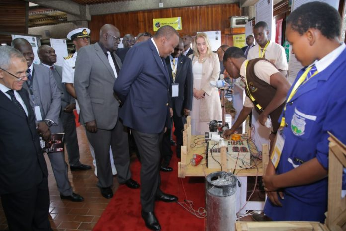 Photo- H.E President Uhuru Kenyatta (Left) looks at an innovation project by students when he opened the second Young Scientists Kenya National Science and Technology Exhibition at KICC, Nairobi, on Saturday August 3, 2019. The President encouraged the key stake holders to help commercialize these great innovations .