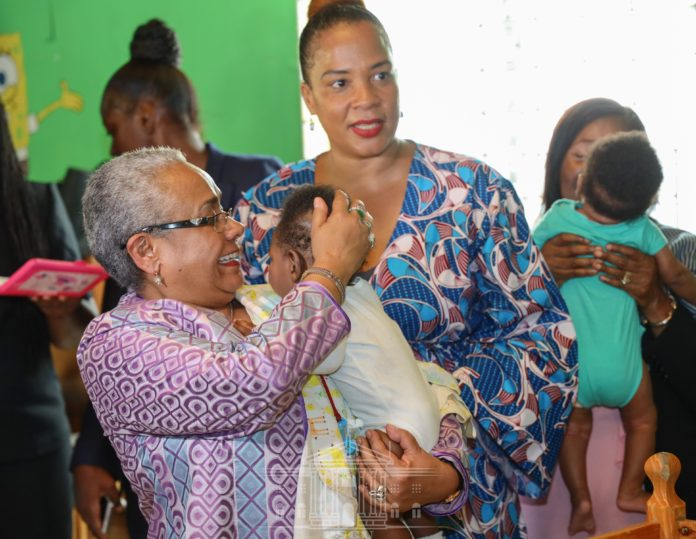 Photo- Kenya's First Lady Margaret Kenyatta (Holding a baby). She is advocating for the reintegration of teenage mothers into schools to give them a chance to complete their education.