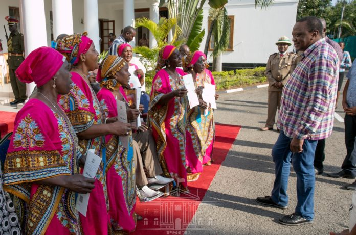 President Uhuru Kenyatta, right, has met and rewarded members of the legendary Mwakigwena Choir Group from Gombatu in Kwale. As part of the government's reward, each of the 14 members of the group has been allocated 3 acres of land at the Bunguni Settlement Scheme in Kwale County.