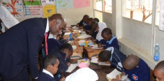 The Director General, Department of Basic Education in the Republic of South Africa Hubert Mweli follow a lesson in grade three class room at the Visa Oshwal Primary School. SA Government wants Kenya to help it to introduce Kiswahili in her schools. Photo/ Courtesy