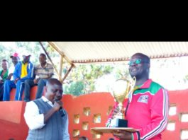 Kisii KUPPET Chairman Laban Bosire, right, poses with one of the trophies donated by the teachers' union leadership during this year's County Term One Championship. On the left is Kisii Sports Committee Secretary Nyantika Geoffrey.